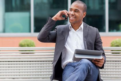 African American man sitting on a park bench reading sleep apnea reviews