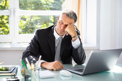 A man sits at his desk and is experiencing sleep apnea side effects