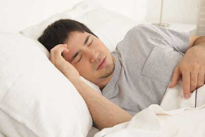 Man sleeping in bed with sleep apnea symptons