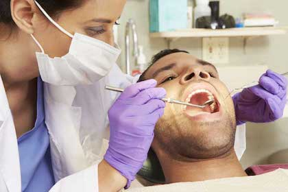 A dentist examining a patient's mouth for sleep apnea symptoms