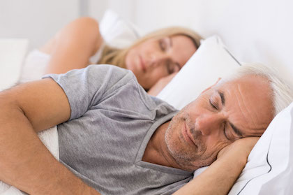 Husband and wife peacefully in bed after sleep apnea treatment