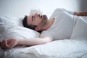 Man trying to sleep but suffering from sleep apnea