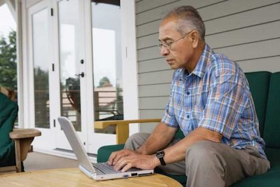Elderly man searching about sleep apnea on his laptop on his outdoor deck