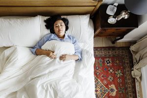 A woman laying in bed suffering from sleep apnea symptoms